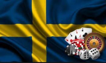 Spelkort, spelmarker, tärningar och ett roulettbord med en svensk flagga i bakgrunden.